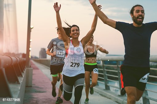 Runners running marathon in the city. They are running over the bridge at sunset. Wearing numbers on their sport clothes. Smiling. Running through the finish with arms raised.