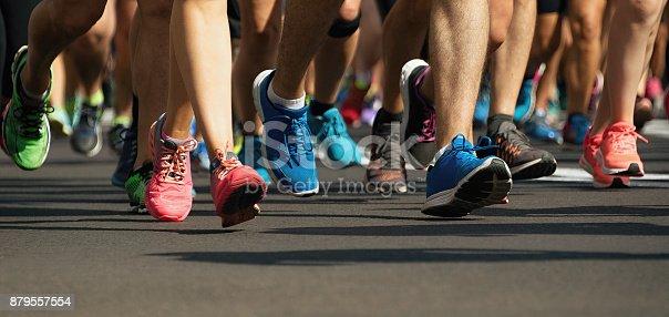 istock Marathon runners running on city road 879557554