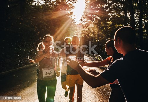 Group of athletes participating in marathon race at sunset and refreshing themselves with cold water.