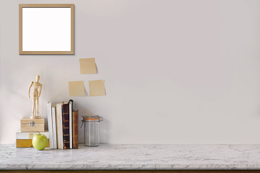 Marble desk with books, blank white picture frame, puppet and sticky note. Mock up