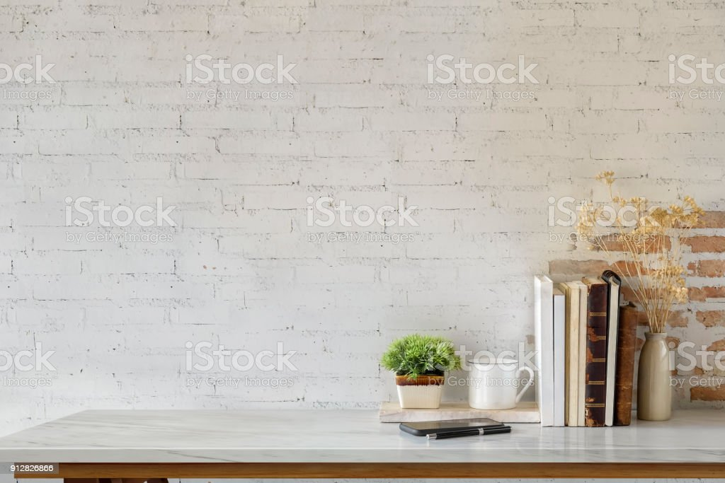 Marble desk with books, coffee mug, mobile phone and plant. Mock up royalty-free stock photo