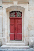 marble away with red door and ornate wrought iron work above door