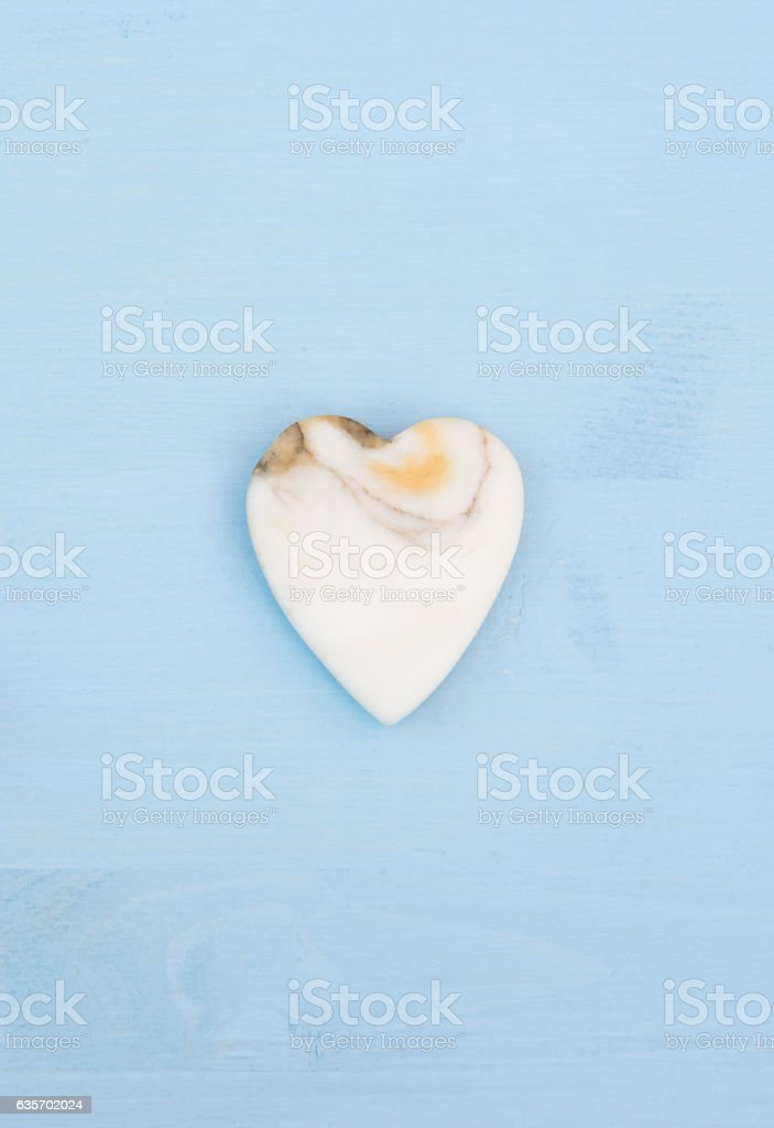 Marble heart on a blue wooden table royalty-free stock photo
