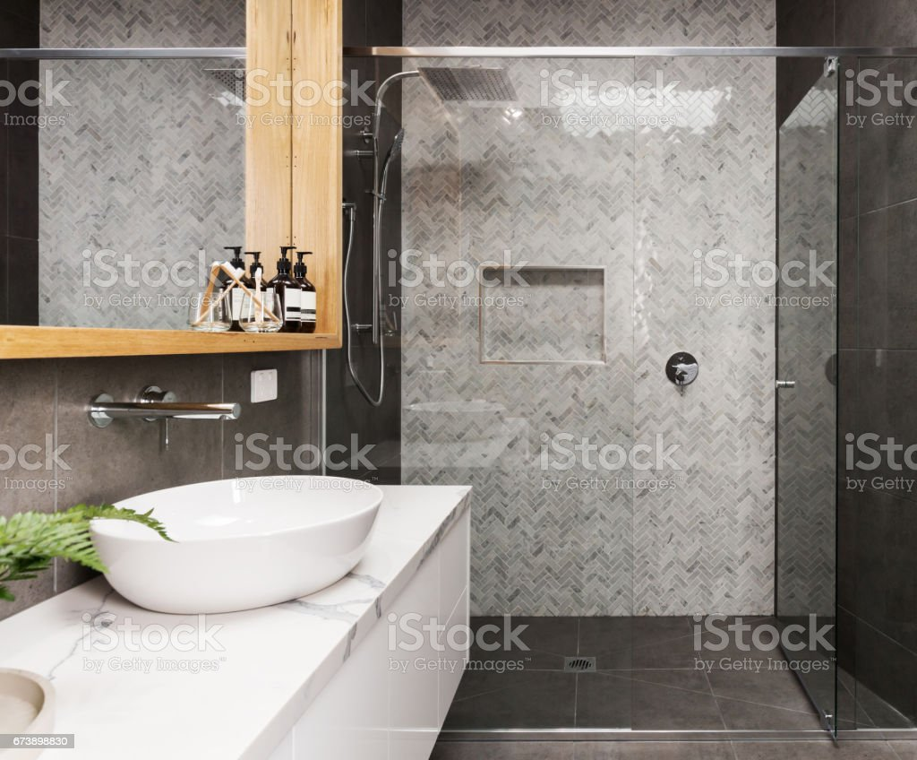 Marble mosaic herringbone tiled shower feature wall in a contemporary ensuite bathroom Marble mosaic herringbone tiled shower feature wall in a contemporary ensuite bathroom Architecture Stock Photo