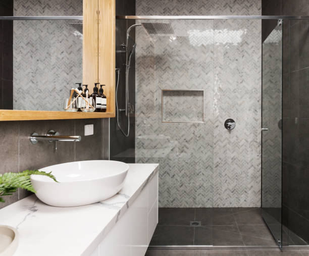 Marble mosaic herringbone tiled shower feature wall in a contemporary ensuite bathroom stock photo