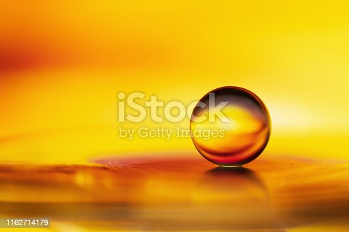 Marble on glass plate in yellow golden background. Abstract background
