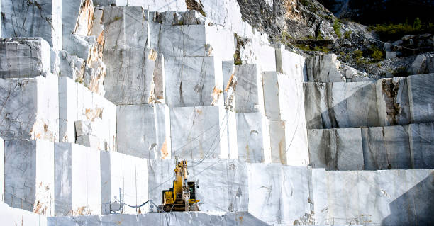 Marble quarry in Carrara, Tuscany, Italy The quarries are places where excavation and marble processing takes place for many centuries. For the way in which marble is taken, the wide spaces, the symmetrical precision of the steps, the machining plans, seem to be staged by amphitheatres. quarry stock pictures, royalty-free photos & images