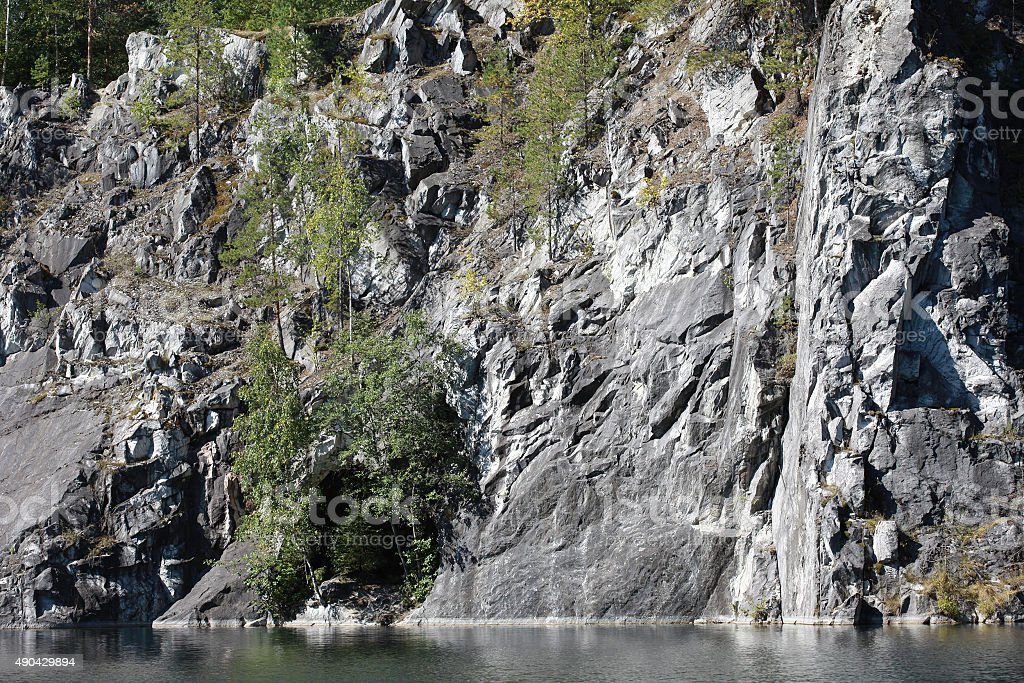Marble rock over water. Rocky shore of the lake stock photo