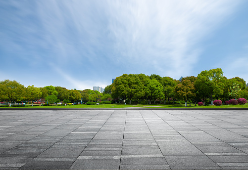Marble square in front of dense woods of city park under clear sky