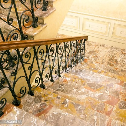 Luxury interior: marble staircase with wrought-iron railing and wooden handrail
