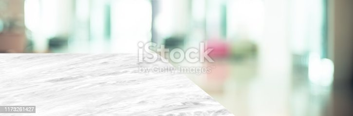 istock marble table top product display background with blur business office hallway.left perspective stone kitchen counter with people waiting doctor in hallway.Banner mockup presentation 1173261427