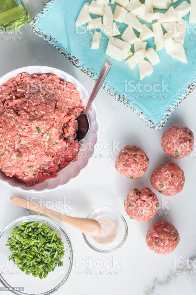 Marble table top with ingredients to make meatballs including raw ground beef, mozzarella cheese, chives and salt stock photo