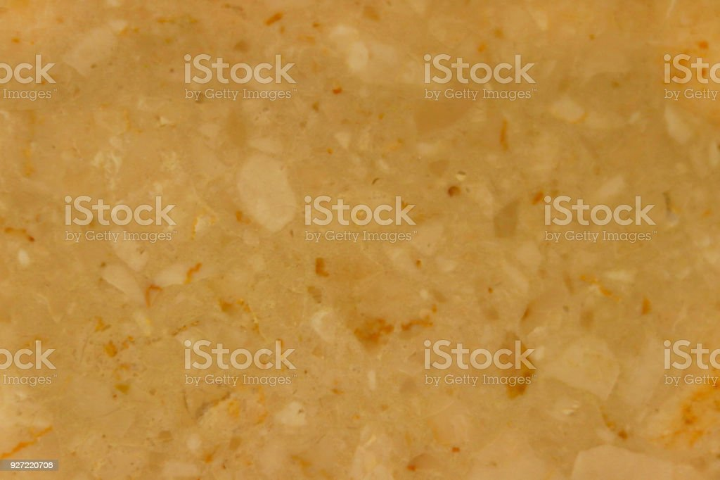 Marble texture. The background is a palyned plate. A product made of stone. Fragments of small stones. Smooth surface with a glossy sheen reflecting light. Soft warm honeyed tone. Orange color. stock photo