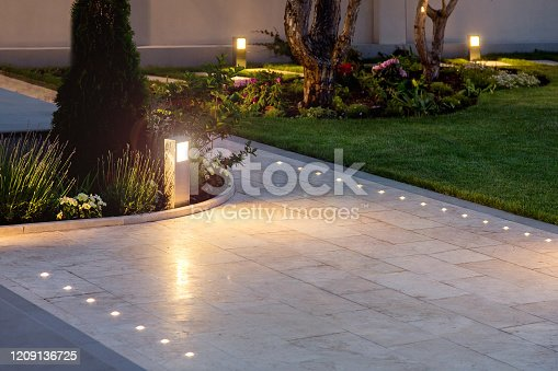 istock marble tile playground in the night backyard of mansion with flowerbeds and lawn with ground lamp and lighting in the warm light at dusk in the evening. 1209136725