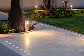 marble tile playground in the night backyard of mansion with flowerbeds and lawn with ground lamp and lighting in the warm light at dusk in the evening.