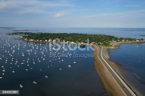 An aerial view of the causeway and harbor alongside Marblehead Neck, Massachusetts. The harbor is filled with pleasure watercraft during summer.