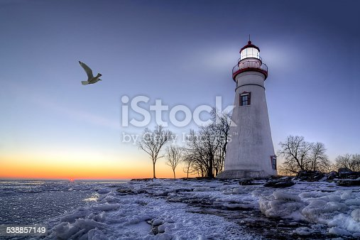 The historic Marblehead Lighthouse in Northwest Ohio sits along the rocky shores of the frozen Lake Erie. Seen here in winter with a colorful sunrise and snow on the ground.