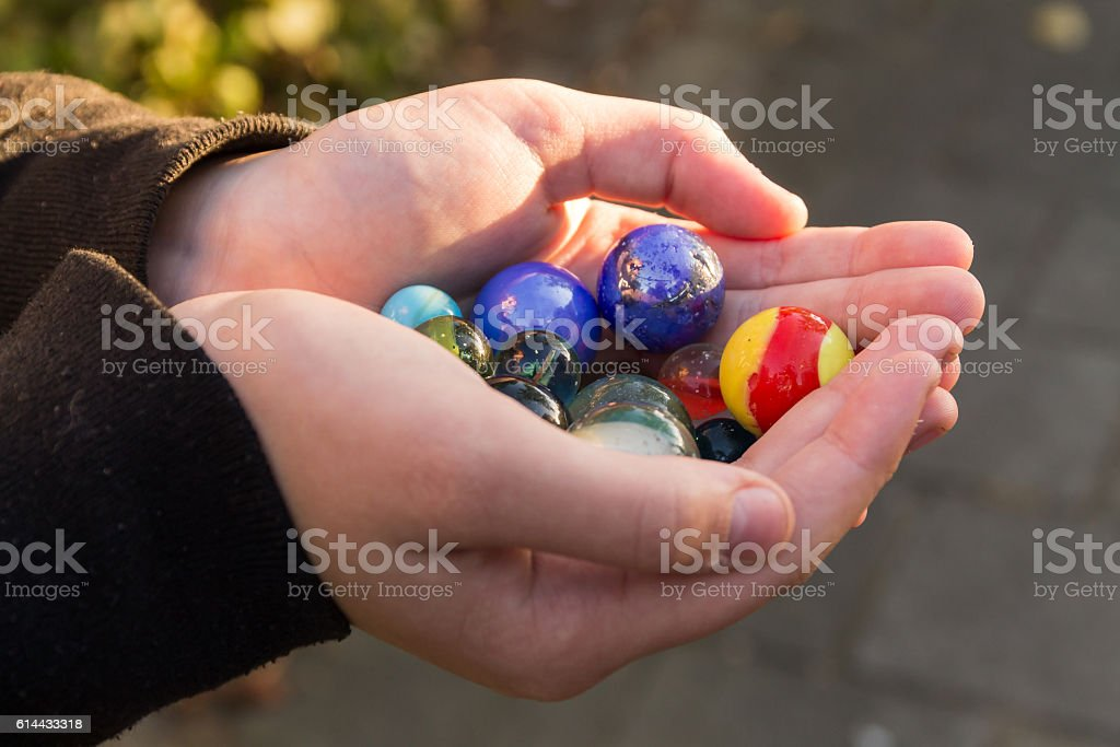 Marbles in the hands of a child. – Foto