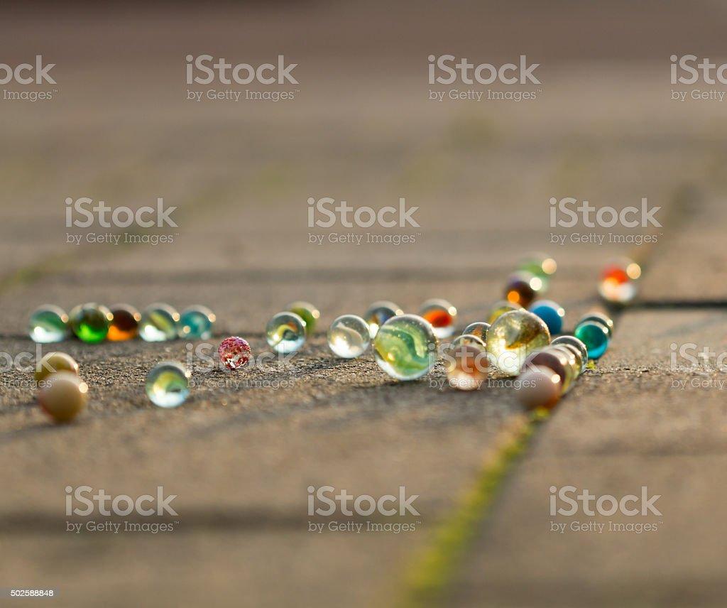 Marbles auf dem Gehweg im goldenen Sonnenlicht. – Foto