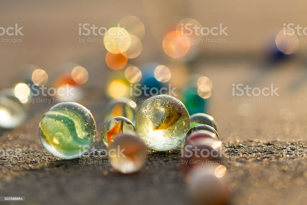 Marbles on the sidewalk in golden sunlight. stock photo