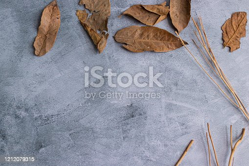 Marbling gray background with dried leaves on the edge