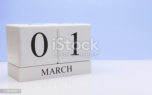 istock March 01st. Day 01 of month, daily calendar on white table with reflection, with light blue background. Spring time, empty space for text 1128783577