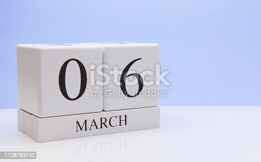 istock March 06st. Day 06 of month, daily calendar on white table with reflection, with light blue background. Spring time, empty space for text 1128783742