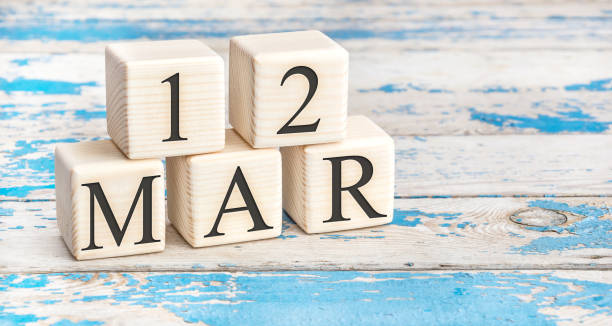 March 12th. Wooden cubes with date of 12 March on old blue wooden background. stock photo