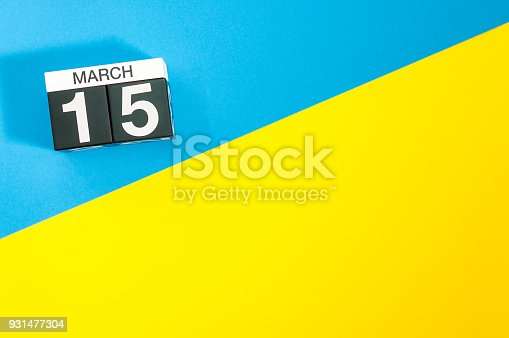 istock March 15th. Day 15 of march month, calendar on blue and yellow background flat lay, top view. Spring time. Empty space for text 931477304