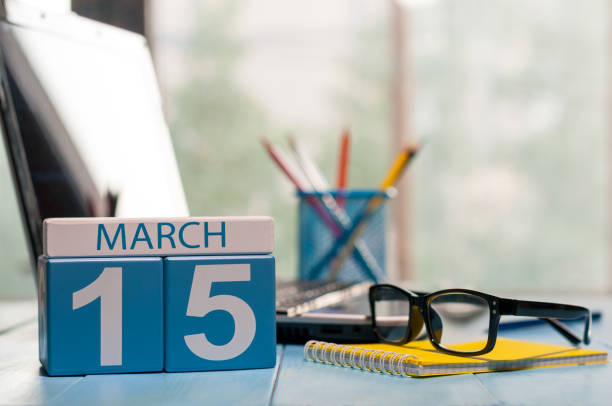 March 15th. Day 15 of month, calendar on business office background, workplace with laptop and glasses. Spring time, empty space for text stock photo