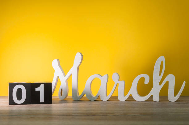 march 1st. day 1 of month, daily wooden calendar on table with yellow background. spring time, empty space for text - welcome march stock photos and pictures