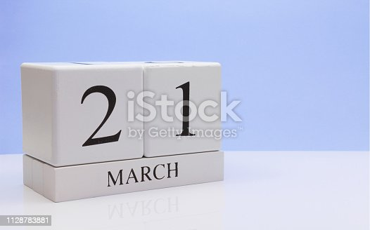 istock March 21st. Day 21 of month, daily calendar on white table with reflection, with light blue background. Spring time, empty space for text 1128783881