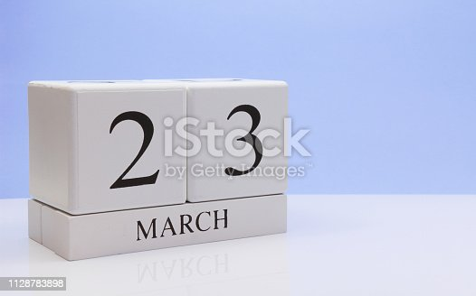 istock March 23st. Day 23 of month, daily calendar on white table with reflection, with light blue background. Spring time, empty space for text 1128783898