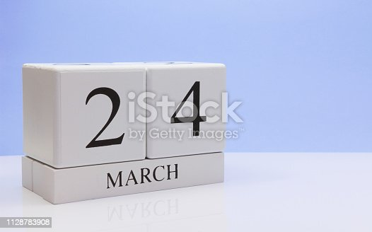istock March 24st. Day 24 of month, daily calendar on white table with reflection, with light blue background. Spring time, empty space for text 1128783908