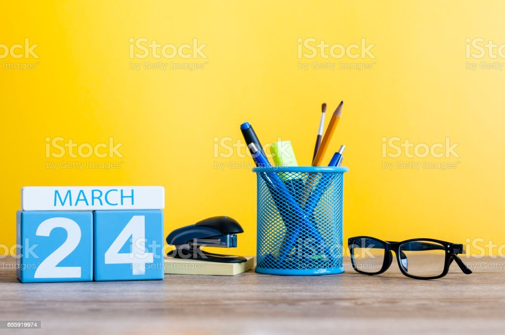 March 24th. Day 24 of month, calendar on light yellow background, workplace with office suplies. Spring time, empty space for text stock photo