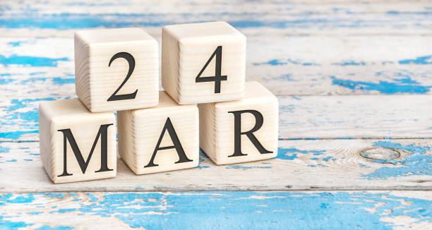 le 24 mars. cubes en bois avec la date du 24 mars sur le vieux fond en bois bleu. - nombre 24 photos et images de collection