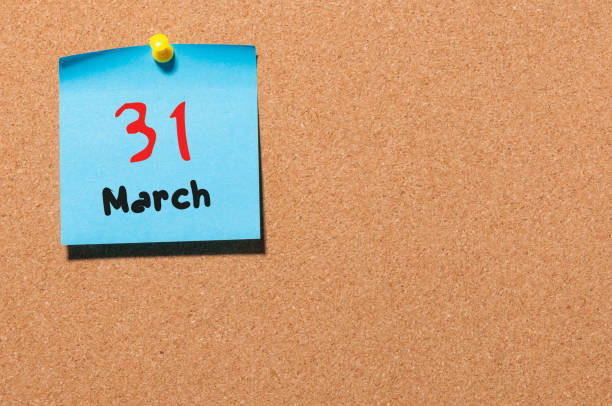 March 31st. Day 31 of month, calendar on cork notice board background. Spring time, empty space for text stock photo