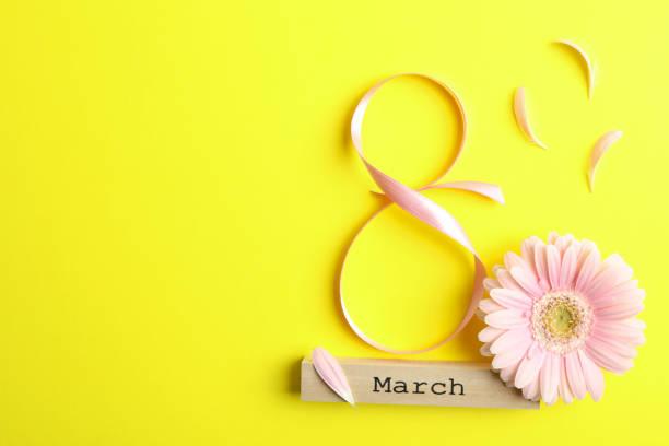3月8日, 國際婦女節。圖8粉紅色的絲帶與美麗的 gerbera 在黃色背景。文本的空間 - womens day 個照片及圖片檔