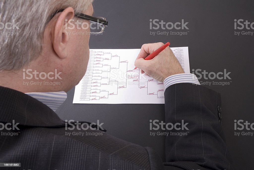 March Madness Businessman Crossing Out Teams on Bracket stock photo