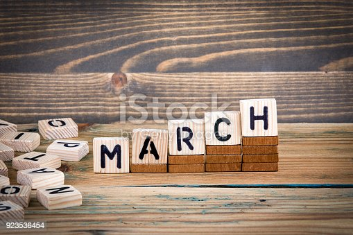 istock March. Wooden letters on the office desk, informative and communication background 923536454