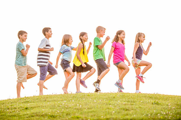 Marching on a Hill Top A multi-ethnic group of elementary age children are marching in a row on a hill top together on a sunny day at the park. marching stock pictures, royalty-free photos & images