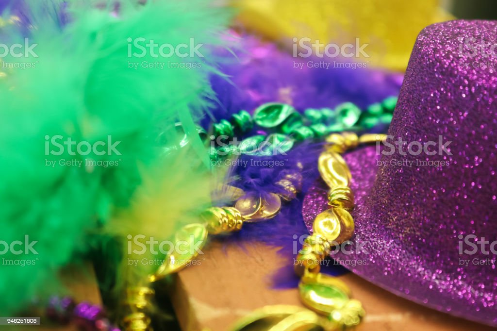 Mardi Gras background in green and shades of purple and gold with...