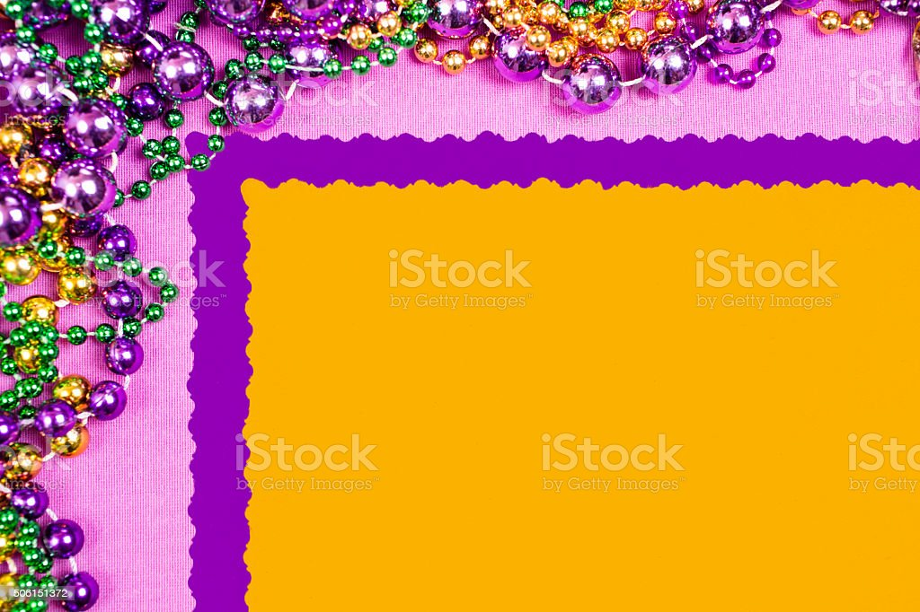 Mardi Gras background. Colorful beads in purple, gold, and green...