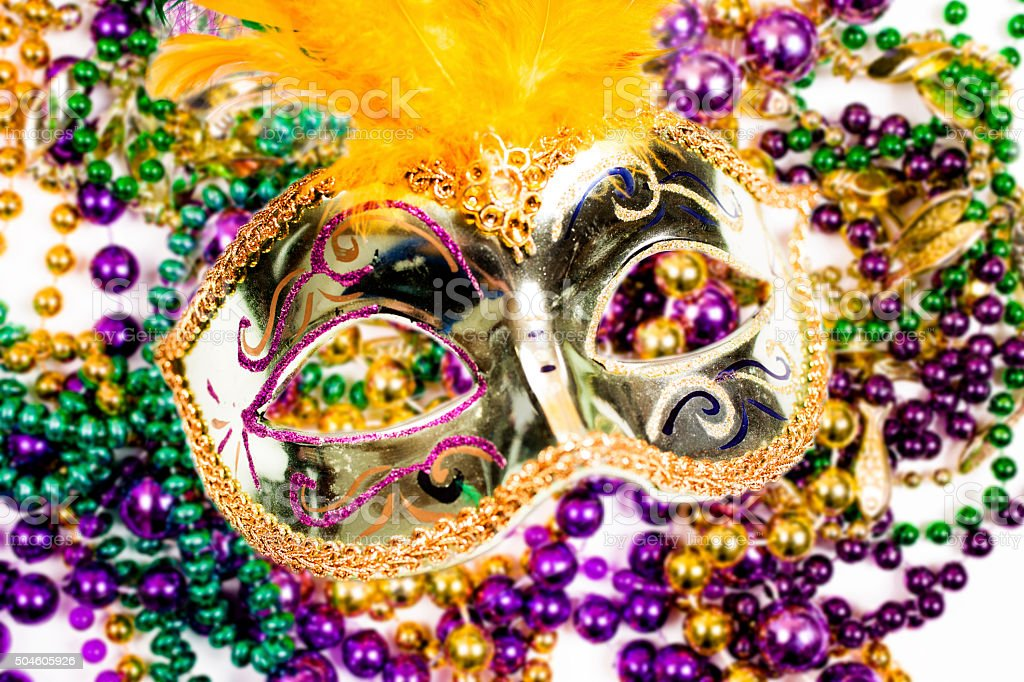 Mardi Gras background. Colorful feathers decorate the beautiful gold...