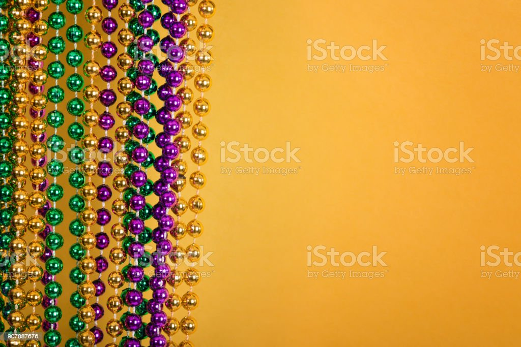Mardi Gras beads against golden yellow background stock photo