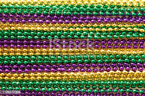 Rows of gold, purple, and green Mardi Gras beads.