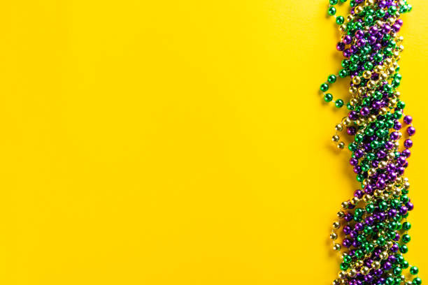 mardi gras carnival concept - beads on yellow background - koralik zdjęcia i obrazy z banku zdjęć