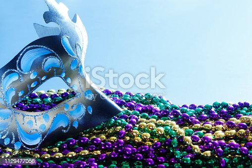 A Mardi Gras mask and a pile of colorful beads in front of light blue background.