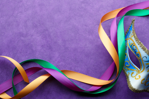 Mardi Gras mask and colorful ribbon on purple background