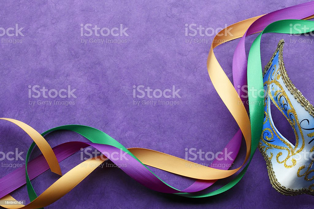 Mardi Gras mask and colorful ribbon on purple background stock photo